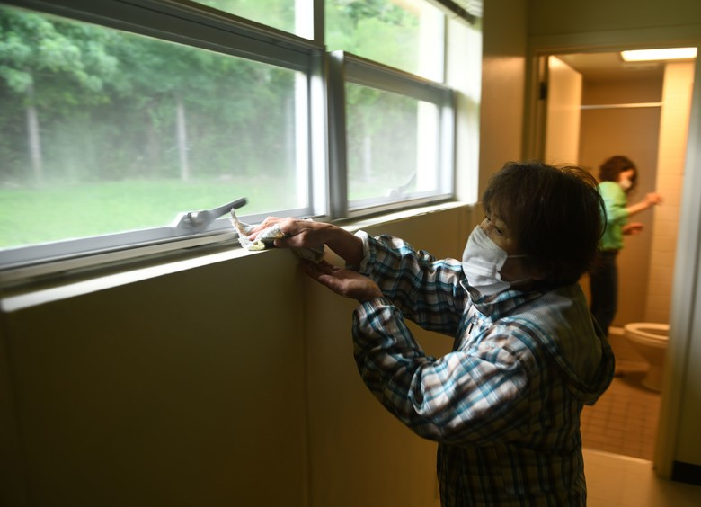 A woman wearing facemask while removing dust in the window