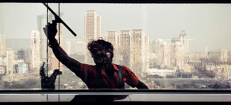 A professional window cleaner cleaning the window glass of the building