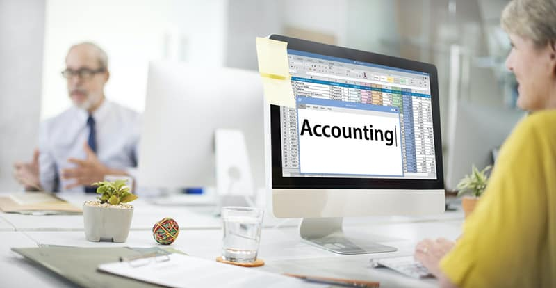 Accountant working on accounting spreadsheet in office