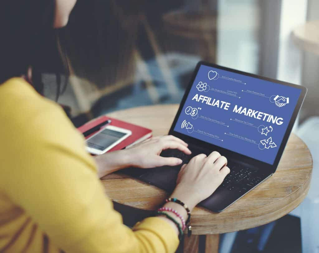 woman wearing yellow jumper typing on laptop - affiliate marketing tips showing on screen