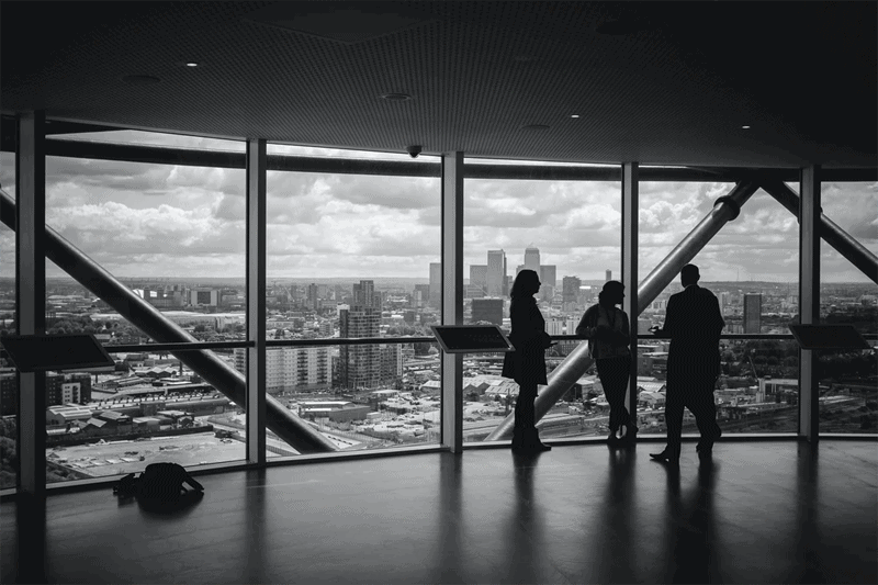 People having a marketing meeting looking out over city landscape