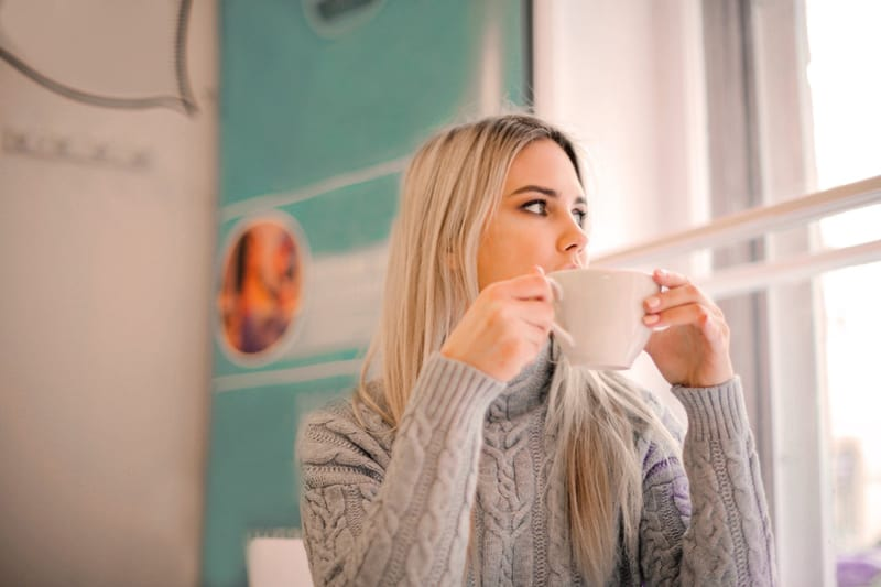 woman in gray sweater drinking from white ceramic mug look out of the window – have a break to be more productive