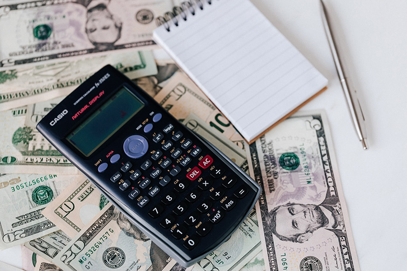calculator, note pad and pen placed on stack of USA dollar bills