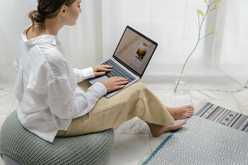 Woman using a laptop sitting on a bean bag