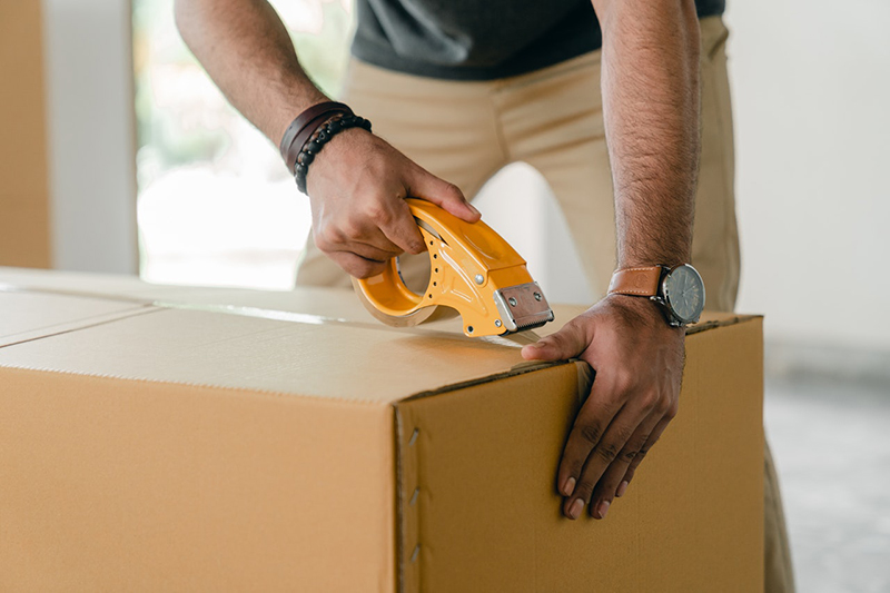 close cropped image of man taping carrying box with scotch tape – moving relocation