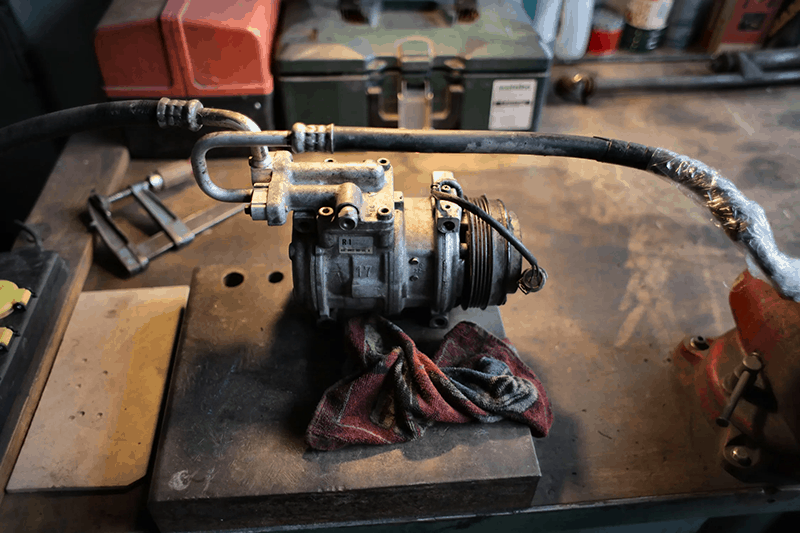 A metal air conditioning compressor on workbench in garage
