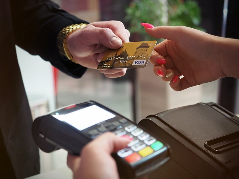 A man handing the credit card to a woman