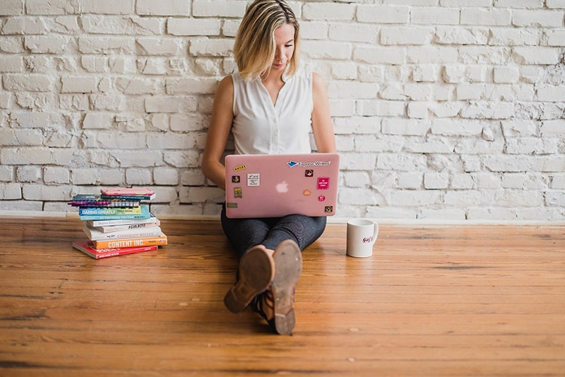 A young woman sitting in the floor while working on her pink laptop