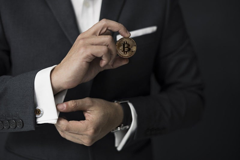 Man in dark suit and white shirt with cufflinks - holding a bitcoin cryptocurrency