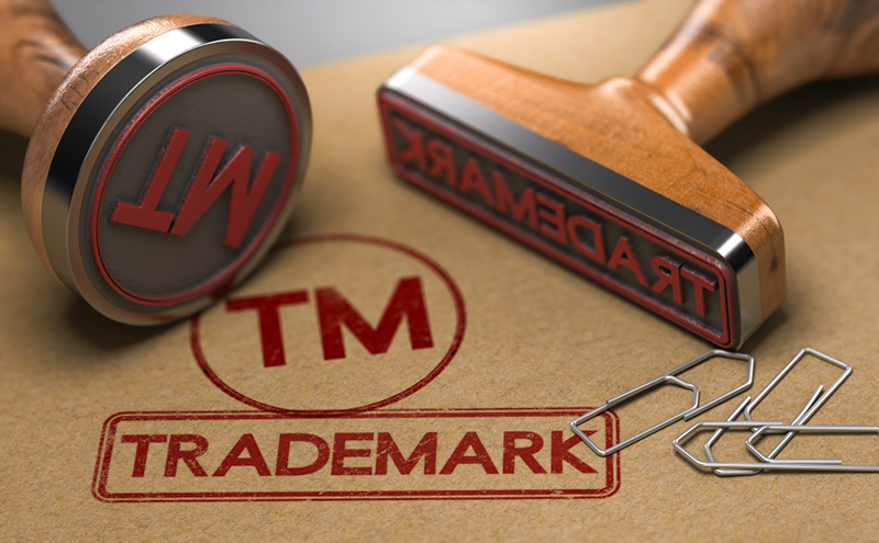 Trademark and TM stamped onto brown paper using Trademark and TM rubber stamps