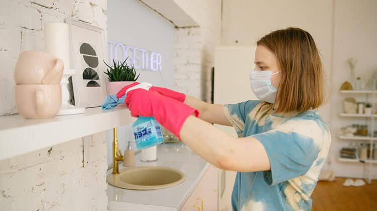 A woman wearing facemask while cleaning