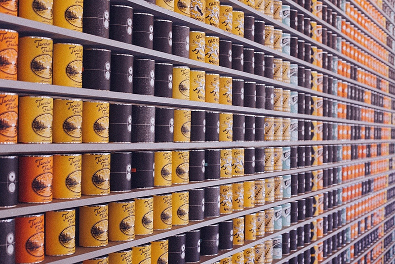 multiple rows of cans stacked on shelves