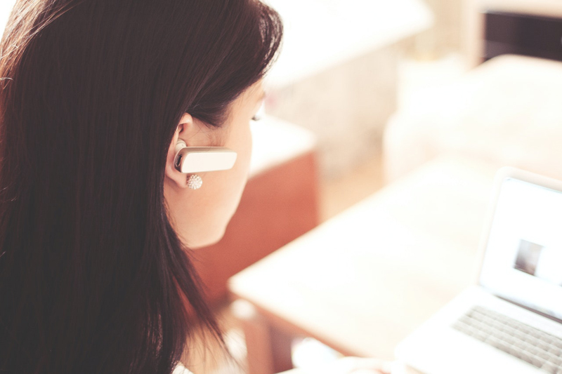 female customer support agent wearing earpiece and using a laptop