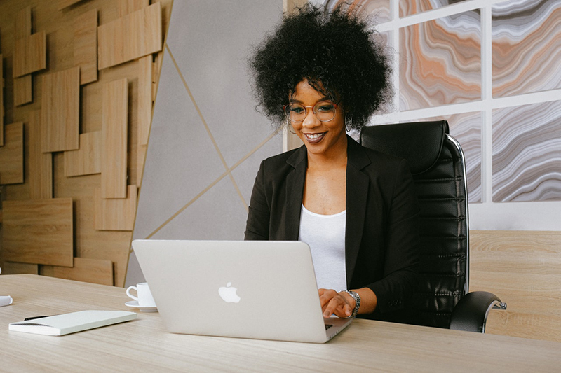 Woman in black blazer sitting at a desk using a Macbook