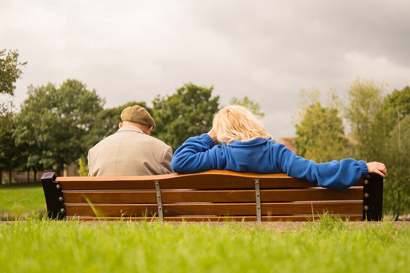 Man and woman sitting and resting on a bench in a park