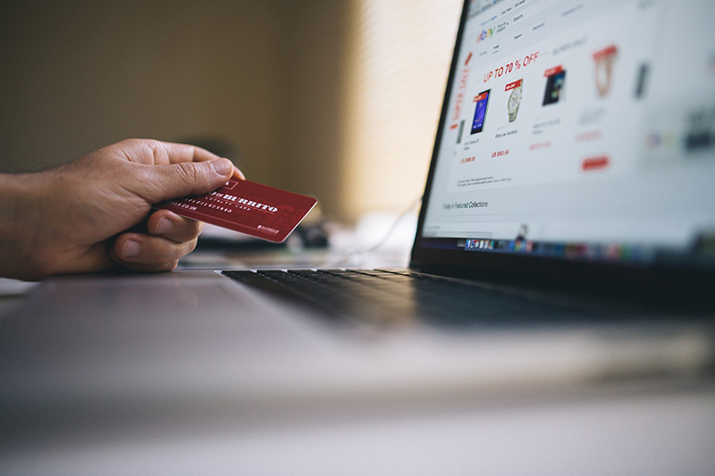 A person holding credit card in front of laptop screen