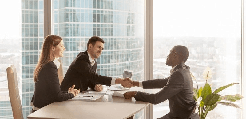 People shaking hands at in an office - enterprise customer support