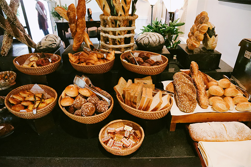 Different kind of bread on brown wooden tray