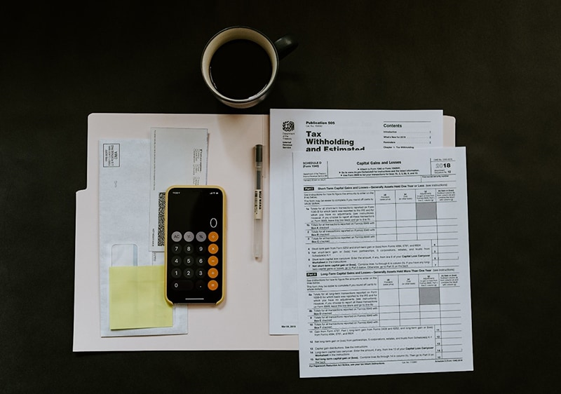Open document folder containing tax information next to calculator, pen and cup of coffee