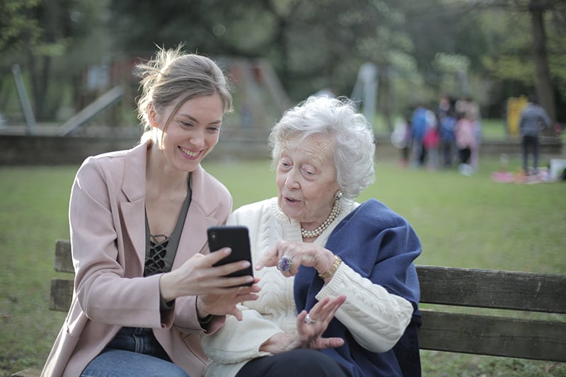 Senior mother and adult daughter using smartphone together