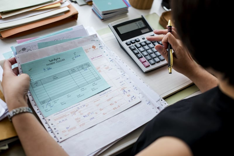 Women using calculator doing accounting and reviewing invoices.