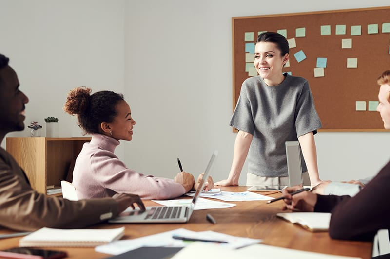 Woman wearing gray shirt standing in front of her colleagues