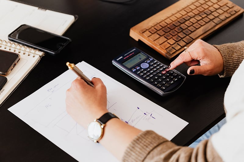 Woman using calculator and taking notes on paper