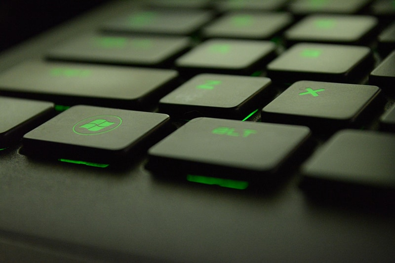 Close up of black keyboard with green back light. Focused on Microsoft window key