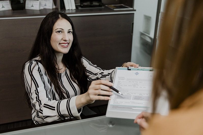 Happy woman handing the contract to the customer