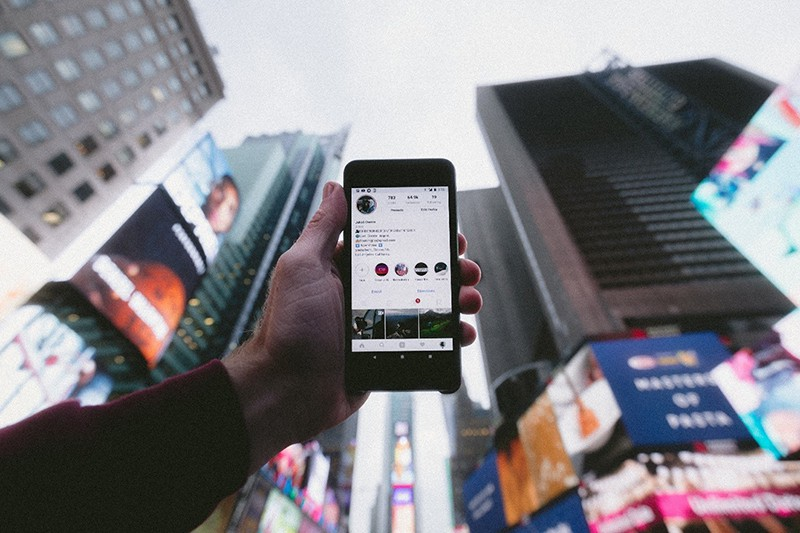person outside point smartphone to the sky showing instagram story