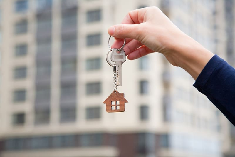 Person holding keys for real estate property on key ring with a little house