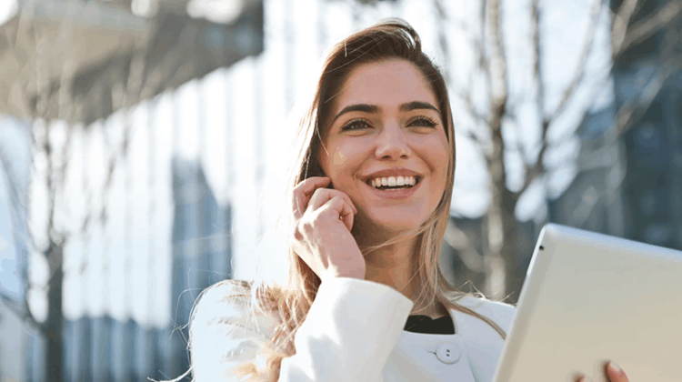 A smiling woman while talking on her mobile phone