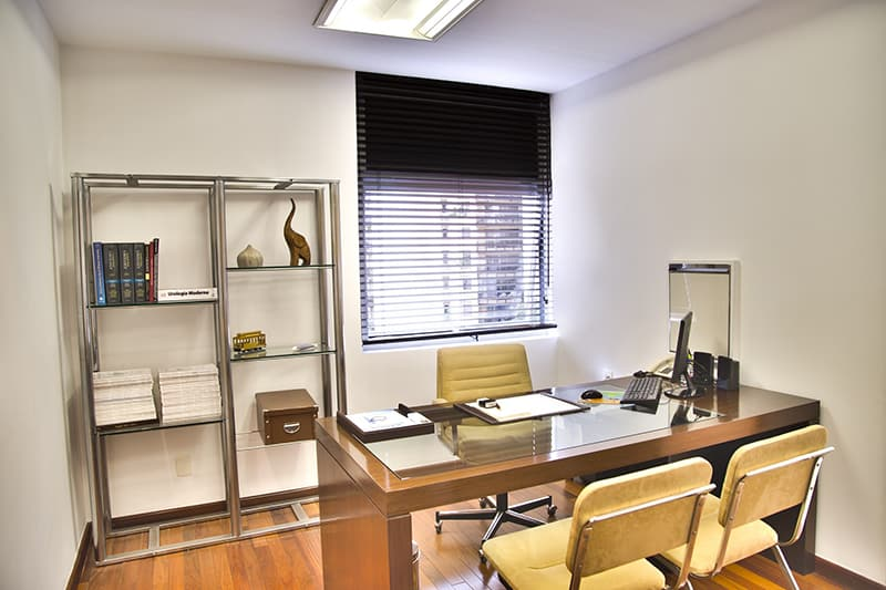 A small office with brown wooden desk