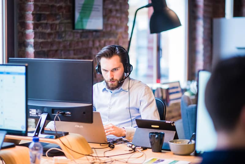 selective focus image of a man in wearing a shirt working in an office on IT project on laptop