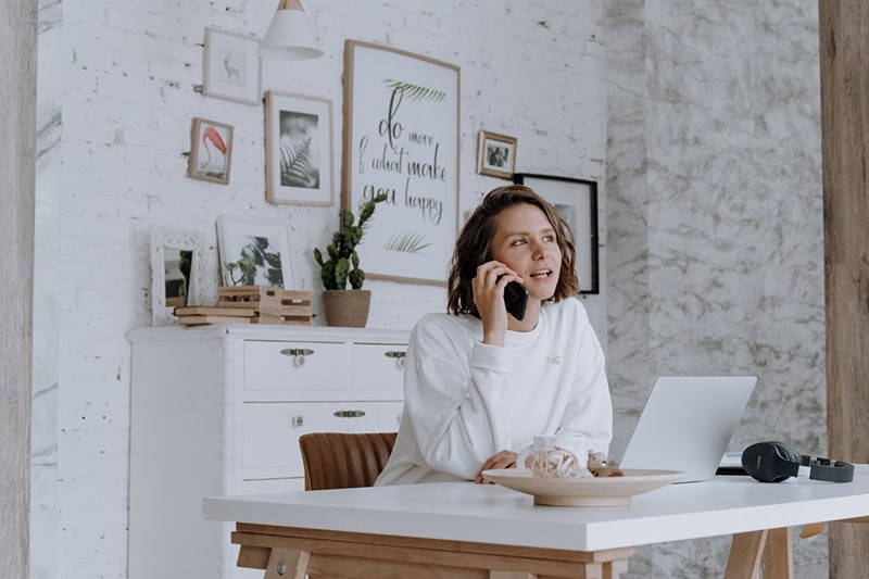 self-employed woman in white top speaking on the phone sat on wooden chair at her desk in front of her laptop