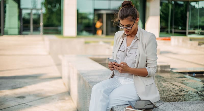 woman dressed in white and light coloured clothing sat on a wall texting on phone