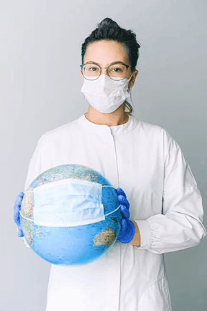 A nurse with eyeglasses wearing facemask while holding a globe