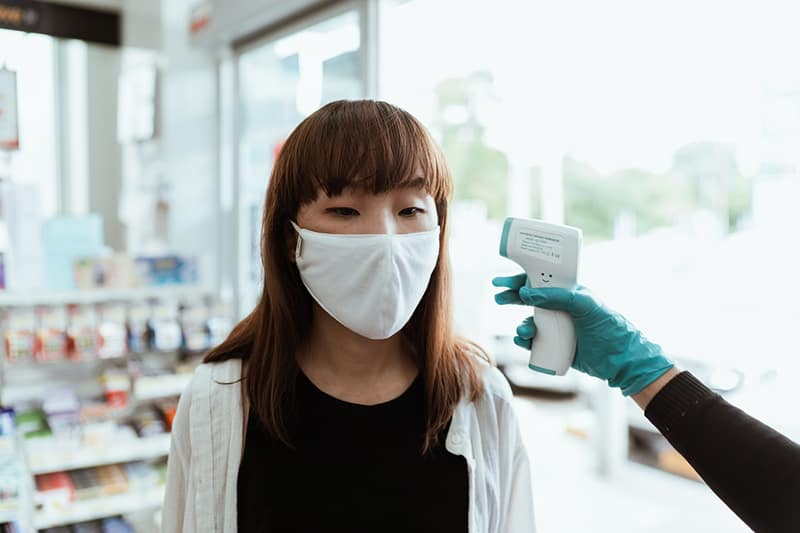 Woman wearing a face mask getting her temperature checked