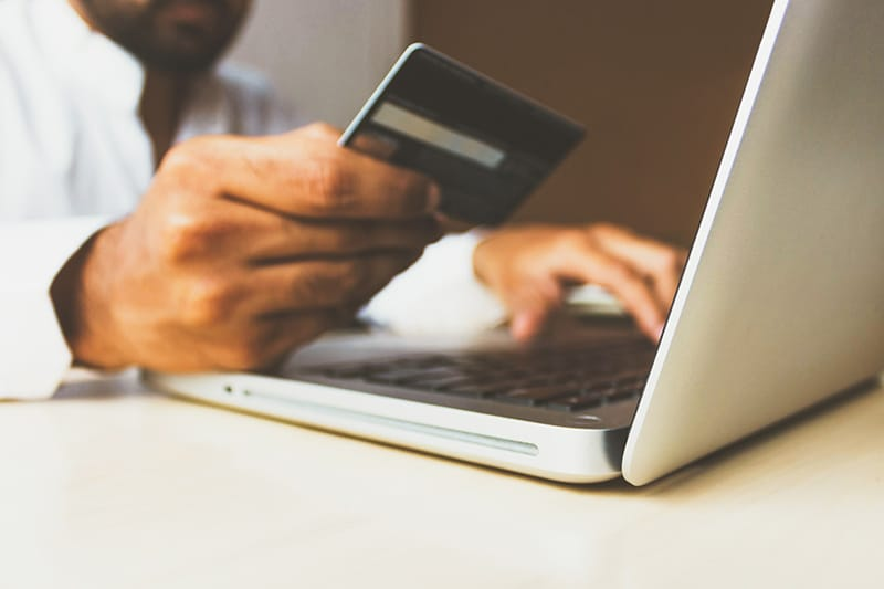 Man with a credit card using a laptop to make purchase from ecommerce business site