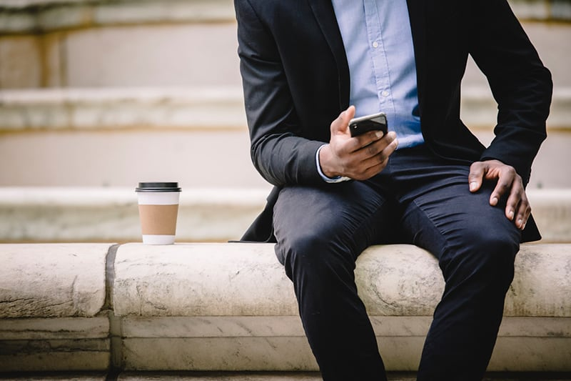 cropped image of businessman using smartphone while resting on a bench