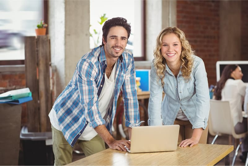 2 employees standing side by side in front of laptop on table in a small business office