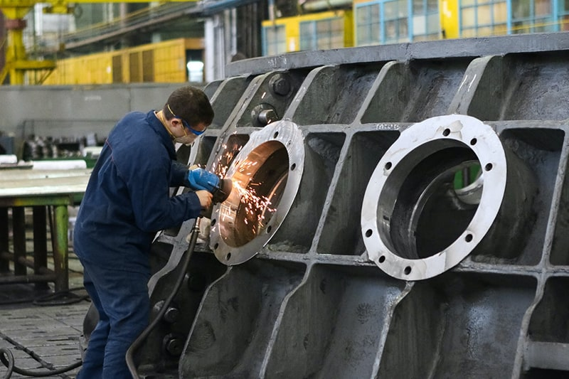 man welding round window frame in manufacturing company