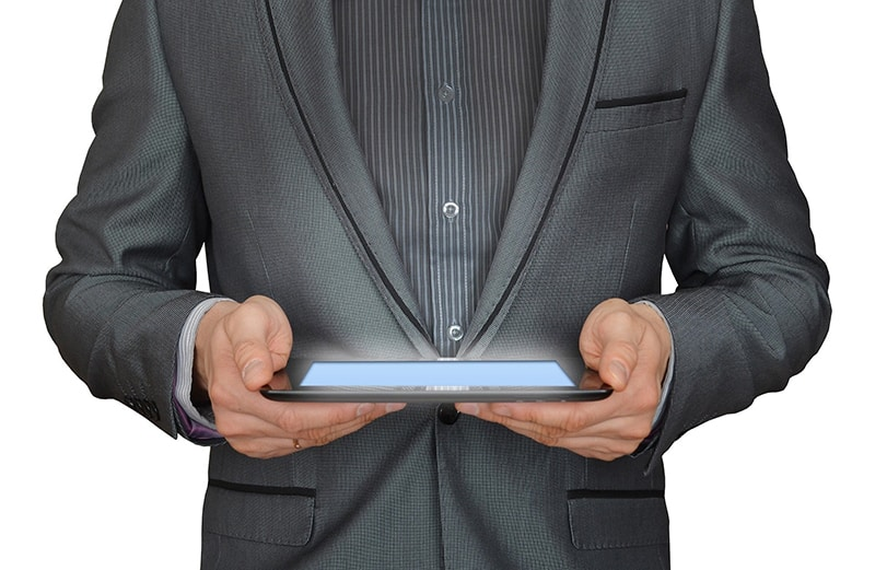 A man in grey suit with tablet on hands