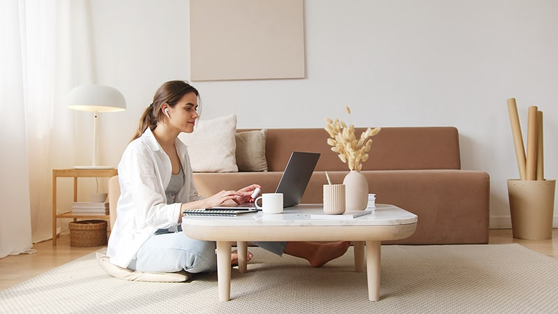 Woman working on her laptop while sitting on the floor