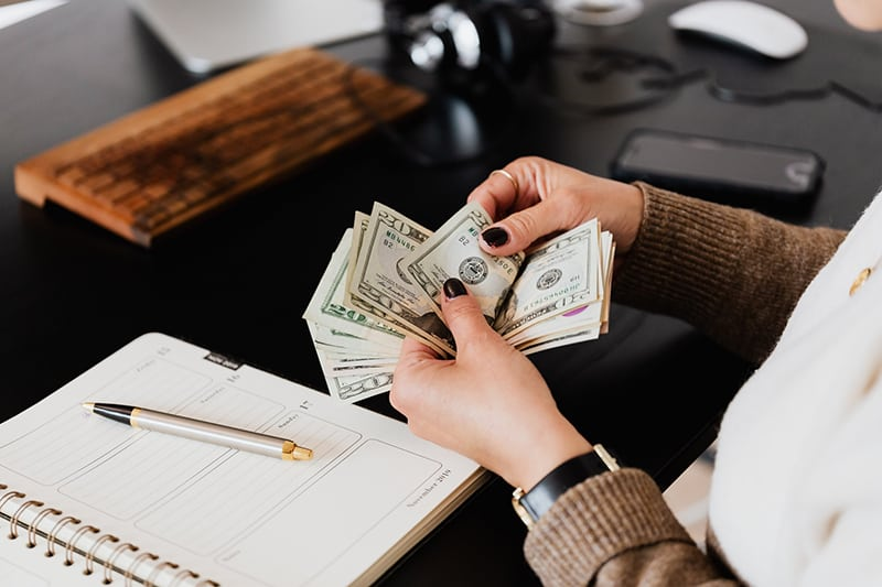 Woman on her desk counting dollars on her hand