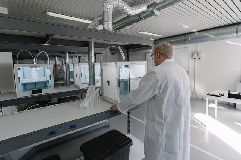man in white laboratory gown in front of 3d printer
