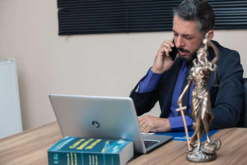 A lawyer on call while working on his gray laptop