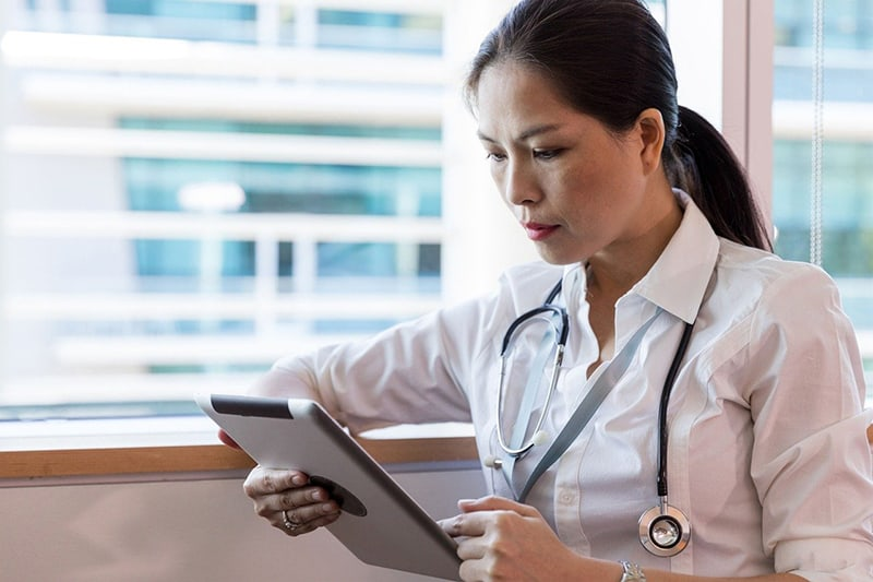 Female hospital worker looking at tablet computer