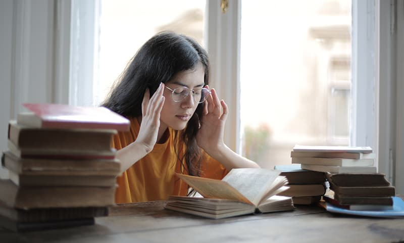Female student suffering headache in the library