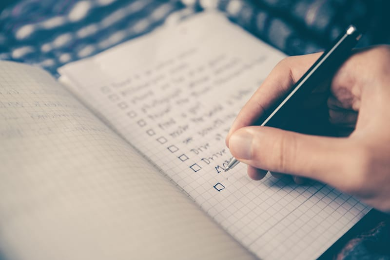 person writing notes checklist in notebook